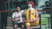 man sitting next to Ronald McDonald statue