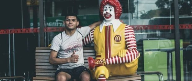 man sitting next to Ronald McDonald statue