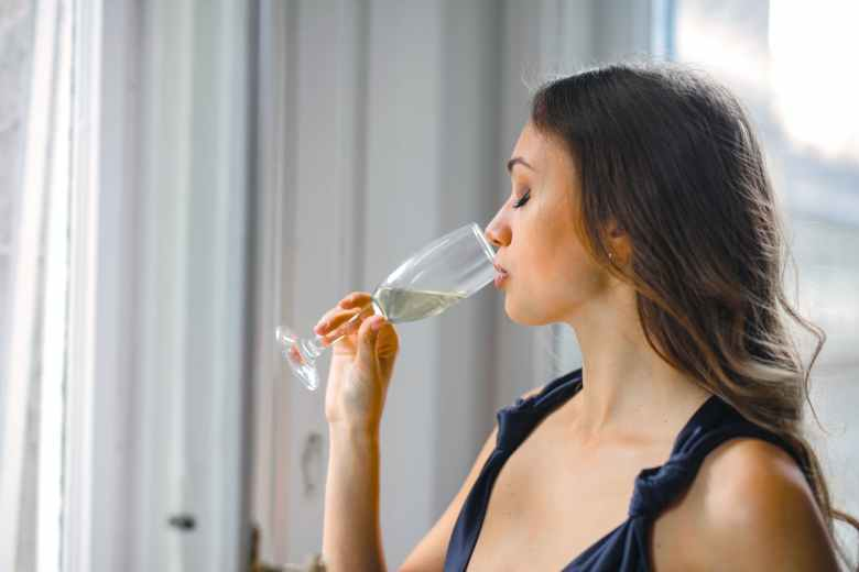 selective focus side view photo of woman in a black top drinking champagne