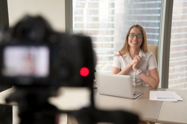 Smiling businesswoman talking on camera - marketing your hospital on Facebook Live video