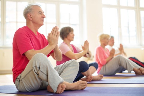 Senior man sitting in lotus position doing meditation with group of people in yoga class