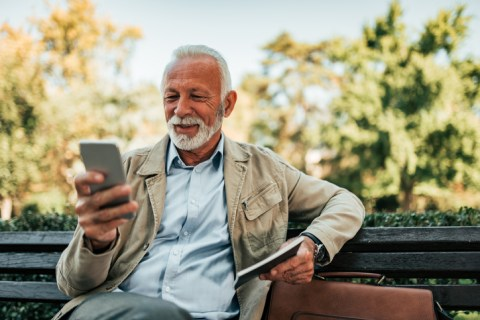 Senior man reading online news on smartphone outdoors.