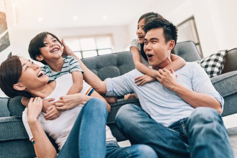 Asian ethnicity family with two children having fun at home