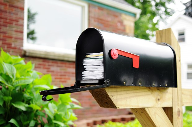 direct mail and letters piled high in a mailbox