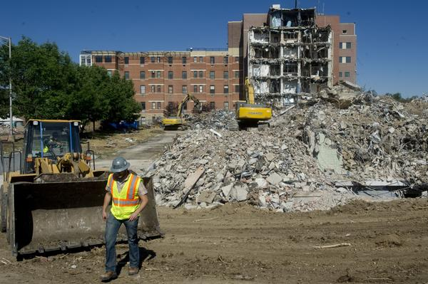 DENVER, CO. - JULY 16: A construction worker walks in front of a bull dozer while excavators pick apart rubble at what used to be the St. Anthony's Central Hospital on July 16, 2013. EnviroFinance is working as the master planner of a 300 million dollar project to redevelop the six square block facility into apartments, shopping, and entertainment. (Photo By Grant Hindsley/The Denver Post)