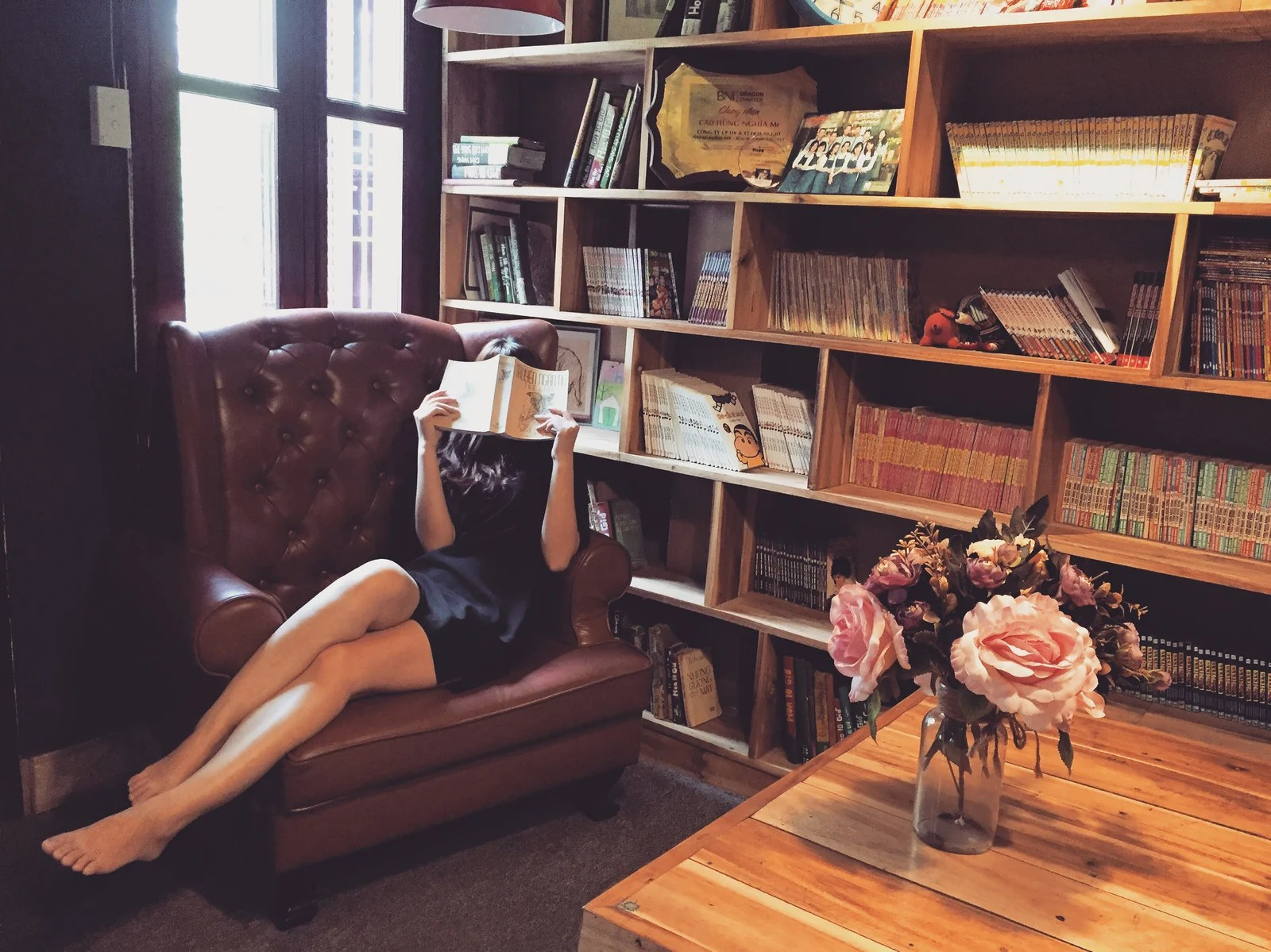 Woman In Black Mini Dress Sitting On Brown Leather Tufted