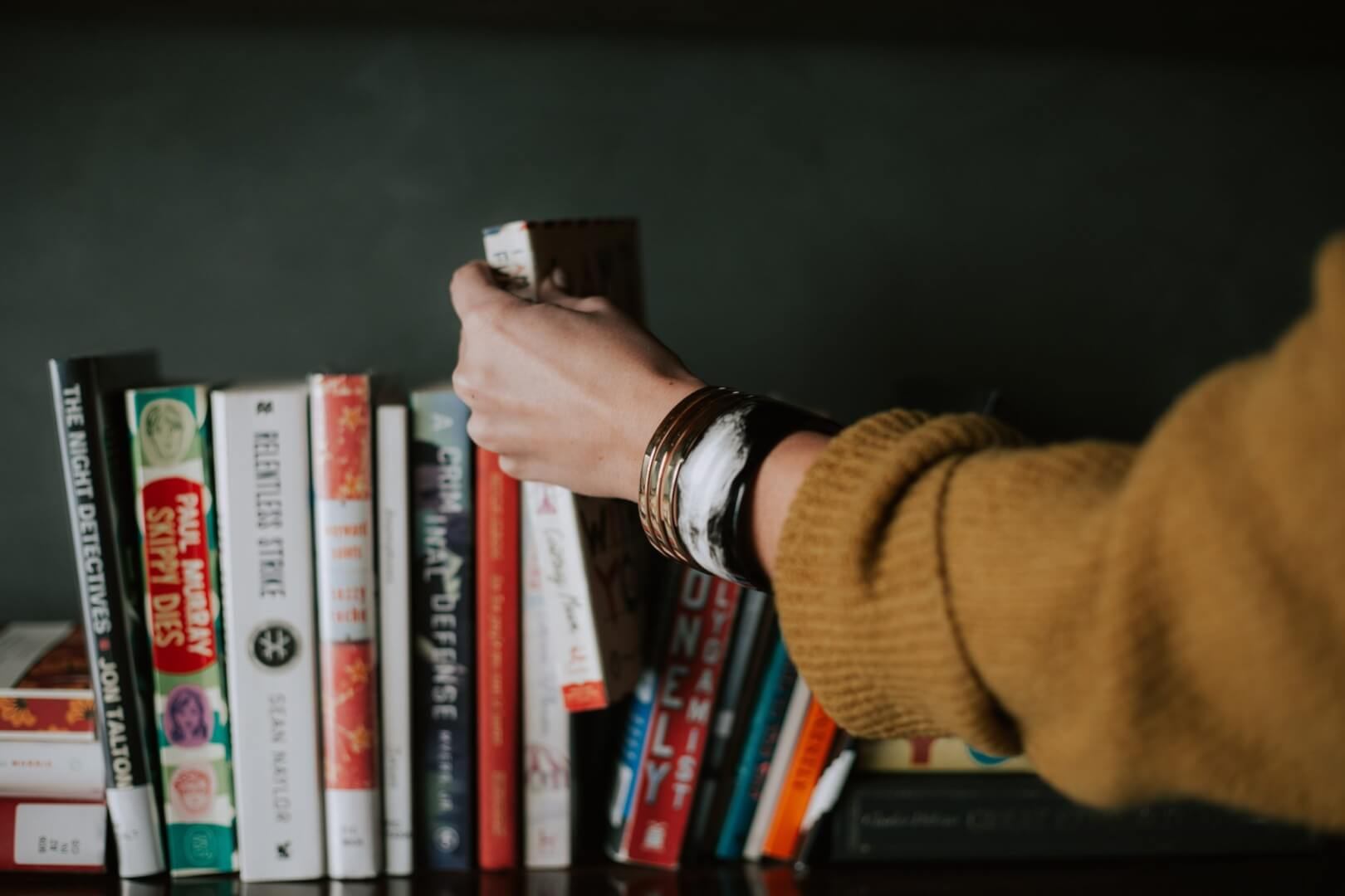 person lifting book from shelf