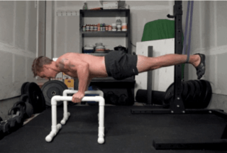 health coach Brian doing an assisted planche on diy parallettes bars