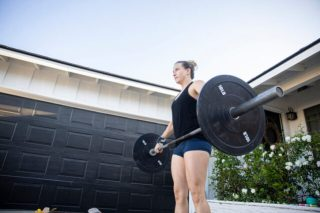 Woman deadlifting with a bar outside her garage