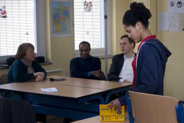 Tiruye steht in ihrer neuen Schule in Berlin, hinter ihr diskutieren ihr Onkel, Lehrerinnen und Gorden Isler über ihre Zukunft.