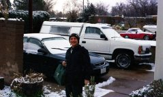 "Janet with her Honda (she's always kept Hondas and she gives them the name ""Hobbit,"" this one in the photo is Hobbit #2 and presently she's driving Hobbit #3 ) -- in front of our house ( I on the other hand have to have a truck, pictured) -- February 24, 2004"