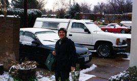 """Janet with her Honda (she's always kept Hondas and she gives them the name """"Hobbit,"""" this one in the photo is Hobbit #2 and presently she's driving Hobbit #3 ) -- in front of our house ( I on the other hand have to have a truck, pictured) -- February 24, 2004"""