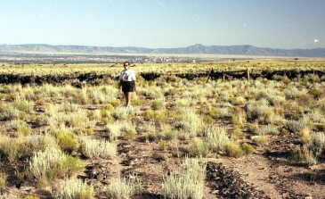 Janet on the West Mesa at Piedras Marcadas petroglyph site with Albuqueque and Sandia Mountains in the distance -- September 7, 1992 -- photo by Mark Weber