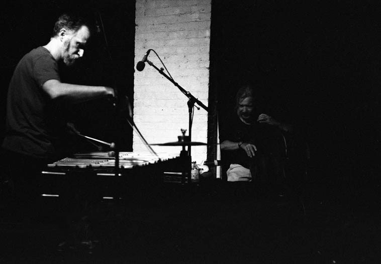 Kevin Norton bowing one of the vibraphone bars with Ed Schuller counting the ways -- August 22, 2014 -- photo by Mark Weber