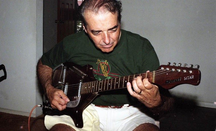 """Michael Anthony at home with his Coral electric sitar-guitar invented by Vincent Bell --  August 12, 1996 -- photo by Mark Weber -- (Michael tells me that he has since sold  this guitar he used so often in the 60s in the L.A. studios) ---- Today we'll spin a little recording  we made in my living room where I convinced Michael that the Downton Abbey Theme was  going to be a hit, or, if I didn't convince him, he was at least nice enough to come over and record  it for the radio show -- we got 3 very different versions in that session, and the one I'll play today  is during soundcheck while Michael was familiarizing himself with the tune as the soundtrack  played we decided to take a pass that way as well, and Michael suggested we call it """"Hanging  Out With the Record"""" -- subatomic particle reducers for real . . . ."""