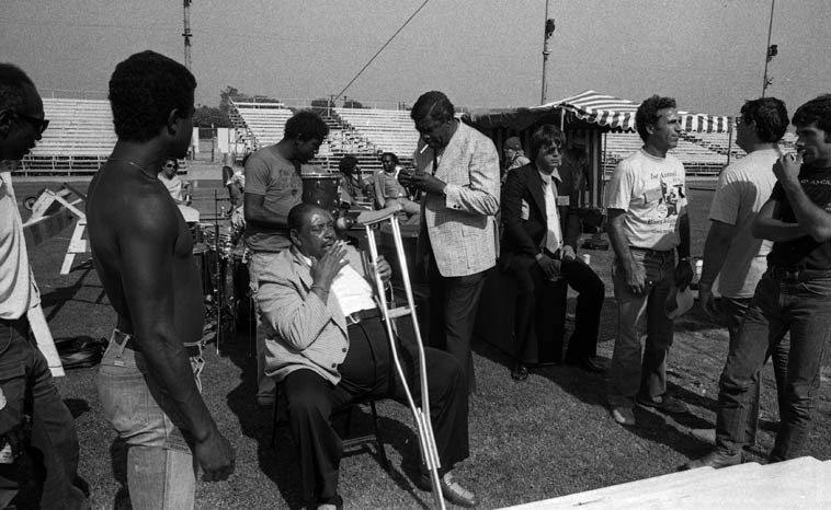 Two poets of the blues having a cig: Big Joe Turner and George Harmonica Smith -- Long Beach, California --  July 20, 1980 -- photo by Mark Weber -- (that's Bernie Pearl with a pencil over his ear) -- KLON first-annual  Blues & Gospel Festival, Veterans' Memorial Stadium
