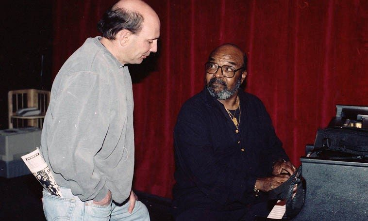 Two tenor saxophonists lean on a piano ---- James Moody showing Tim Zannes the changes  on the Outpost Steinway ---- April 21, 1997 ---- photo by Mark Weber  (Zannes plays both violin  and tenor saxophone and lives in Albuquerque and grew up in Cleveland, Ohio)