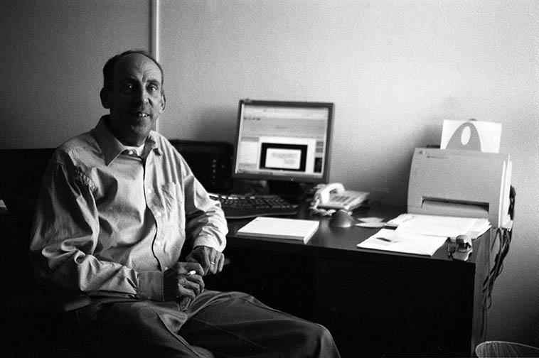 "Richard Towne KUNM General Manager at his desk on the 3rd floor of Onate Hall, campus of University of New Mexico -- July 21, 2o11 -- photo by Mark Weber -- RT will be my pitch partner this Thursday as we scour the airwaves for contributions to keep the station afloat -- I'm always amazed at Richard's ability to balance the varied content that a community radio station must have, his ability to wrap his brain around so many points of view, whereas, myself I need only concentrate on my little corner of jazz . . . . Fortunately, we have a healthy listenership (I'll ask RT for the numbers) that blankets most of the state of New Mexico and only need to fundraise twice a year -- We broadcast in the old-fashioned terrestrial way (new jargon) as well as ""streaming on-line"" 24/7/365 (really new jargon)"