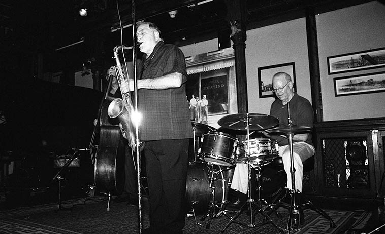 "Kazzrie Jaxen Quartet: Charley Krachy (tenor), Don Messina (bass), Bill Chattin (drums), Kazzrie Jaxen (piano) -- August 24, 2o14 -- photo by Mark Weber -- this music is purely honest, they will not put you on or emotionally manipulate you with grandstanding crescendos, or slow atmospheric long drawn-out build-ups of contrived appointments with a glorious payoff at the end, if you can wait it out (I guess that's what you call a crescendo, eh?) You'll not hear moaning & groaning from the pianist, histrionics, balderdash, psychological meltdowns from the stage, jive is foreign territory here, as is pretension, the drummer won't holler ""Yeh, man,"" to the bass soloist signaling something mysterious has occurred but we in the audience are too unhip to know what just happened, this music brings you along with it or it just isn't happening, you have to be there, this music includes the listener, already there, already in the moment, as they say. Anything else is foreign to these artists."