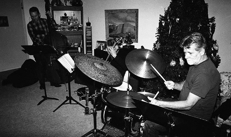 First Take Trio rehearsing with the Christmas tree in Michael & Kathie Anthony's living room -- Michael Glynn (bass) had just flown in from Seattle where he now lives (he was in Albuquerque up through 2o12 completing his masters at UNM Music) -- He had just finished a Pacific Northwest tour with the Louis Hayes' Cannonball Adderley Legacy Project -- photo by Mark Weber -- December 10, 2o15 -- Cal Haines, drumset; Michael Anthony dusting off his old banjo