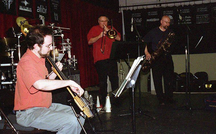 Michael Vlatkovich Quartet in performance at Outpost Performance Space, Albuquerque -- May 19, 2003 -- Chris Garcia(drums), Jonathan Golove(elec-cello), Michael Vlatkovich(trombone), David Mott(baritone saxophone) -- photo by Mark Weber