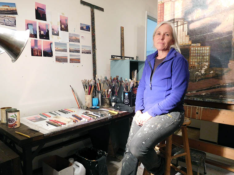 "One of the greatest painters in the West: Sharon Feder in her Denver studio -- October 29, 2o16 --- I've been looking at her paintings ever since I met her sister Janet twenty years ago and was highly-energized to finally meet this artist of luminosity and radiance ---- photo by Mark Weber ---- The Tina Goodwin Gallery that handles Sharon's paintings calls them urban landscapes, or as Tina explained to me more precisely: ""built environments"" -- a lot of shadows falling over deserted streets near railroad tracks and grain elevators, industrial bygone years of Denver, where she was born & raised ---- Sharon is in a phase of painting presently where she partially sands off one of her older paintings that she no longer wants around (her words), then she paints over them, another scene, so that parts of the older painting shows through like a palimpsest -- pure poetry"