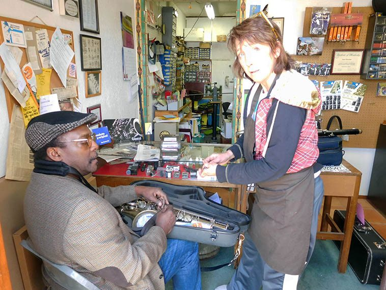 David Murray getting his horns adjusted at Second Wind Repair by Janet Harman, who is a bass player around town and a member of the popular ever-working Albuquerque Cuban-style jazz band Son Como Son -- How a bass player became a master woodwinds repair tech has long been a ponderance of mine ---- photo by Mark Weber -- April 10, 2o17 Albuquerque -- You can see David's bass clarinet behind Janet, and that's his Mark VI in his lap
