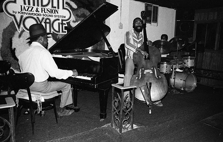 """The Gene Russell Trio at the Maiden Voyage, downtown Los Angeles -- August 23, 1980 ---- Whenever you got caught in L.A. around rush hour, rather than jump on whatever freeway it is you take to get home (there are ten different freeways that converge downtown), and sit in rush hour traffic and let your car over-heat (V8 engines need flowing air to cool them), I'd pop into the Maiden Voyage and kill an hour or two before jumping on the San Bernardino Frwy (10) back to Upland, one of the hundreds of """"bedroom communities"""" that surround L.A. ------------ Here's Gene on piano (a great guy, I always had a good laugh with him); and fellow photographer Clarence Johnston on drums (he tipped me off that taking pictures at the boxing matches at the Olympic was a good score; and our man on bass: HENRY FRANKLIN the Skipper aka Nyimbo, who's still all over Southern California playing that bass and who I just saw in the 2017 restored version of MONTEREY POP (1967) on my favorite set of that flick with Hugh Masekela ----- I'll tell you, when I first saw this film back in 1969 at a little art house on Sunset Blvd, and that huge black African face of Mr Masekela came on the screen like 14-feet across it scorched my white butt back into my seat as he shouted that wordless healing chant, still one of the strongest parts of that documentary, and Henry pulsing and swaying the time like a wave"""