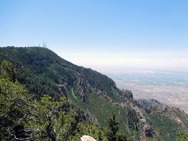 Top of Sandia Peak overlooking Albuquerque and Rio Grande -- July 3, 2o17 -- photo by Mark Weber ---- KUNM's radio tower is among those in the cluster that broadcast all over New Mexico ------ Albuquerque is an island city in the middle of a giant desert -- No other metropolitan area for 500 miles in either direction: El Paso to the south, Denver to the north, Dallas to the east, and Phoenix to the west ----- Nothing but rattlesnakes, scorpions, black widows, wasps, fire ants, yoga fanatics, vampire bats, wolves, cactus, and tarantulas between here and there, only the thorny survive