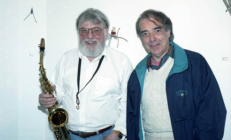 Two refugees from the studios of Los Angeles: Bud Shank & Michael Anthony ---- April 7, 1997 Albuquerque when Bud was in town to play at the Outpost, where this photo was blinked in the art gallery -- They played on many sessions together in the 70s ---- photo by Mark Weber (driftwood assemblages by Deborah Cole in the Inpost Art Gallery)
