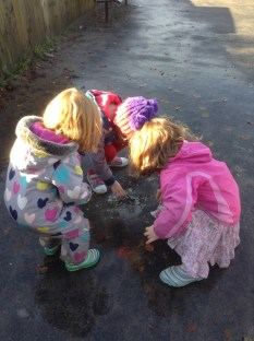 Trying to free a worm from beneath a frozen puddle.
