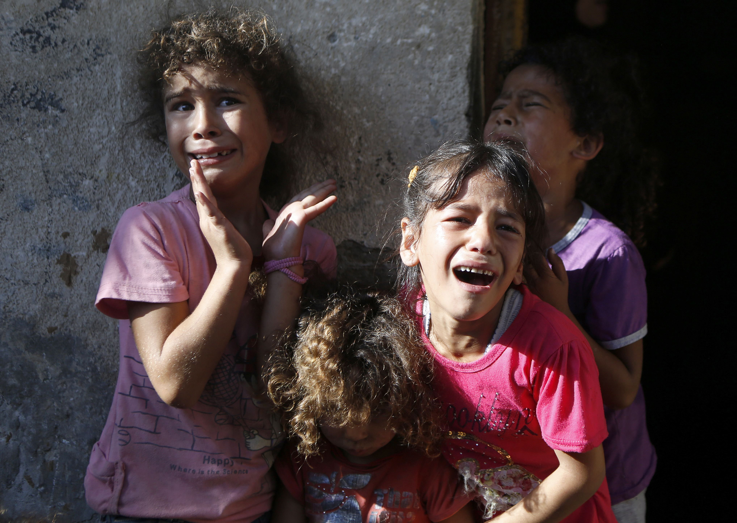 Young relatives of four boys, all from the Bakr family, killed during Israeli shelling, cry during their funeral in Gaza City, on July 16, 2014. Four children were killed and several injured at a beach in Gaza City medics said, in Israeli shelling witnessed by AFP journalists. The strikes appeared to be the result of shelling by the Israeli navy against an area with small shacks used by fishermen. The deaths raised the overall toll in nine days of violence in Gaza to 213. AFP PHOTO / MOHAMMED ABEDMOHAMMED ABED/AFP/Getty Images