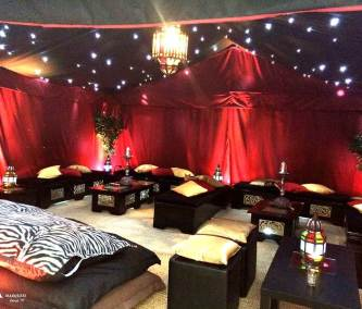 Image of Arabian Nights Themed marquee interior deep satin reds, gold cushions, exotic ceiling lightining
