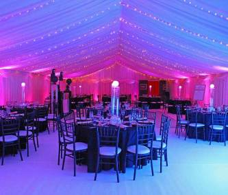 Interior of corporate marquee with black table and chair decor, pink and blue lighting