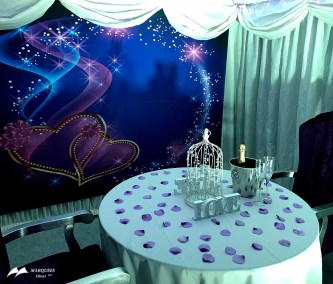 Valentine themed marquee with rose petal tables, heart image walls, satin curtain screens with ruched swags
