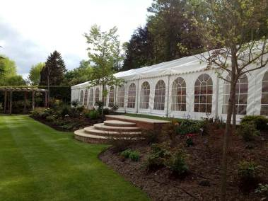 Image of wedding marquee with steps leading down to a terrace lawn