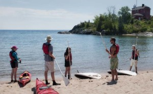 YMCA stand-up paddle boarding instructor Lucas Townsend (right) shows students how to get set up for paddle boarding on Lake Superior. They are pictured here at McCarty's Cove in Marquette, MI. (photo by Ron Caspi)