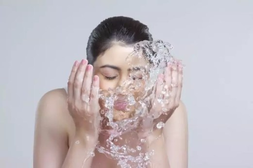 Beautiful woman washing face with water over gray background