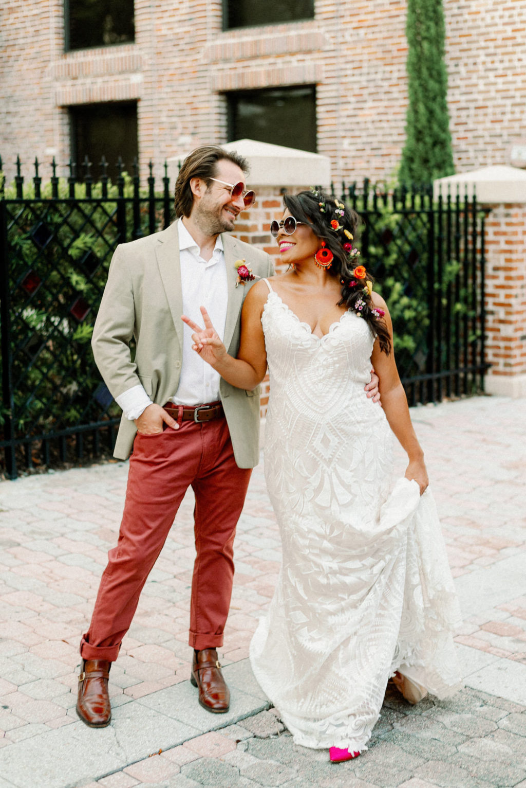 Whimsical Bride Wearing Lace Boho Spaghetti Strap and V Neckline Wedding Dress, Hair in Braid with Colorful Flowers and Sunglasses, Groom in Dusty Red Pants, Gray Suit Jacket and Red Retro Sunglasses   Tampa Bay Wedding Photographer Dewitt for Love