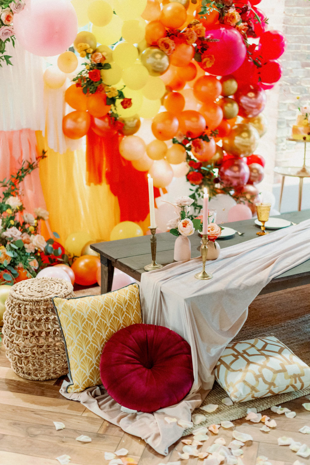 Whimsical and Colorful Wedding Reception Decor, Low Boho Style Picnic Table with Neutral Silk Table Linen, Red, Yellow and Gold Cushions, Woven Basket, Orange, Yellow, Pink, Gold and Fuschia Balloon and Fringe Backdrop, Tall Candlesticks, White Rose Petals   Tampa Bay Wedding Photographer Dewitt for Love   Wedding Linen Rental Kate Ryan Event Rentals