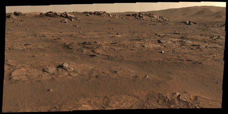 This is a colored image of the rocky, sandy surface of Mars. Large rocks and hills can be seen further away. Closer up rocks are embedded in the surface. This panorama is seen here in natural color.