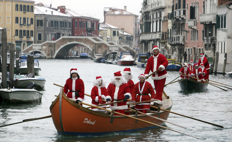 People dressed as Santa Claus row boats on the Venice canal