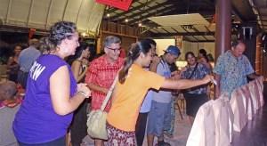 Jambo Arts President Angela Saunders (left) and Marshallese Be Like Film Festival attendees cast their votes for favorite films shown at Jitak En Likatu Bar Friday. Photo: Hilary Hosia.