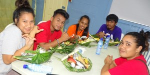 "Students enjoy the local food in their ""enra"" (woven food baskets) as part of their Marshallese Studies course. Photo: Kelly Lorennij."