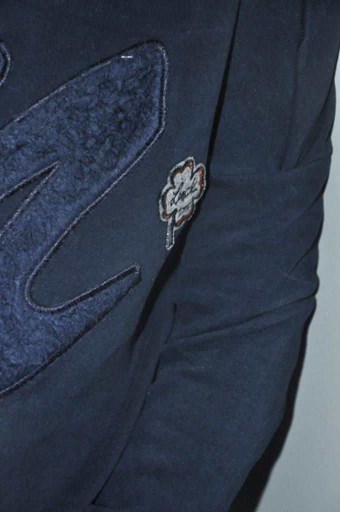Detailfoto van het klavertje 4 met de tekst 'Luck'.