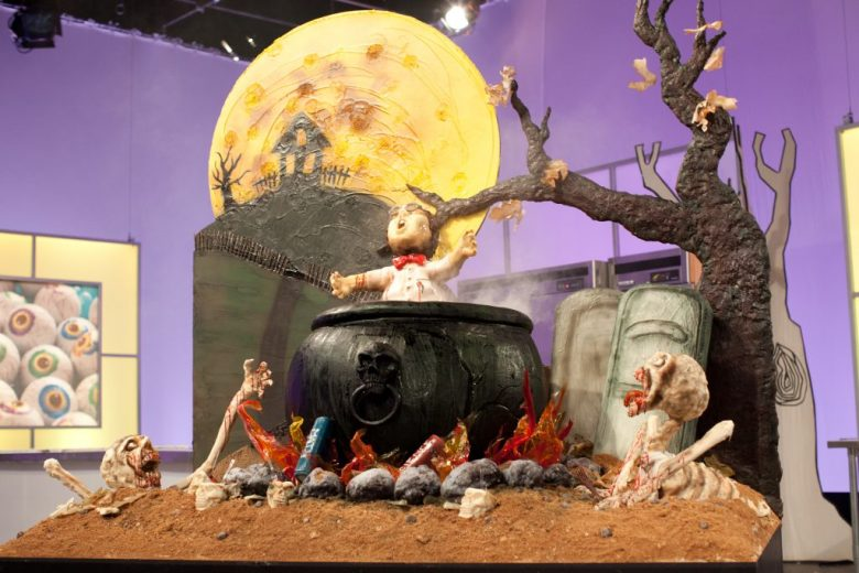 """A man boils in a cauldron in the Orange team's creation called """"Little Alvin"""" made during the final """"spine chiller"""" challenge, as seen on Food Network's Halloween Wars, Season 5."""
