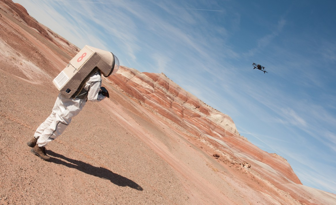 Picture of ou crew engineer in his spacesuit working to map the area with his drone.
