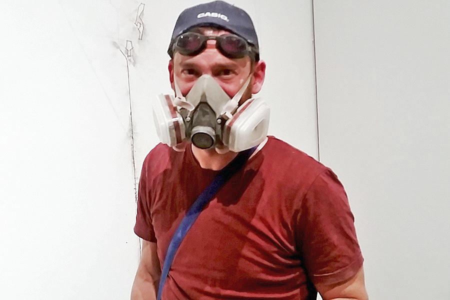Christoph Weber mit Atemschutymaske bei der Arbeit an seinen Wandrityungen fuer die Marta Ausstellung der fremde Raum