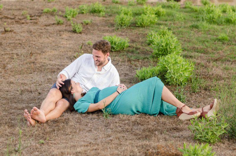 Fotografía de una pareja. Ella está embarazada y tumbada con su cabeza sobre las piernas de él, que está sentado en el suelo. Ambos se están mirando y él le está acariciando la cabeza