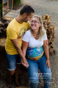 Fotografía desde arriba de una pareja cogida de la mano mirándose en la que se resalta el diseño pintado sobre la barriga de la mamá embarazada. Es un diseño personalizado de una familia tiburón, incluyendo al perro mascota de la familia